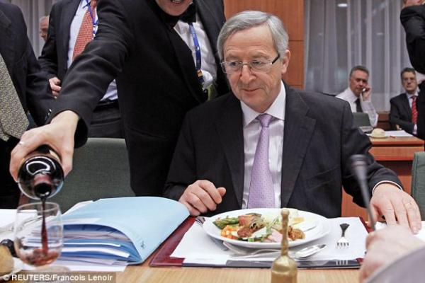 J.C. Juncker's beady, greedy eyes are firmly fixed on the goodness emerging from the wine bottle… Photo credit: François Lenoir / Reuters